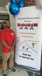 Coach standing by a KiDsGyM USA banner